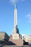 Riga, Lettland - 10. August 2014 - Ehren-Solider-Schutz stehen das Freiheits-Monument unter bewölktem Tag in Riga, Lettland berei lizenzfreie stockfotografie