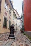 RIGA LETTLAND - AUGUSTI 19, 2016: Narrow lappad grändTroksnu iela i mitten av Riga, Latv royaltyfria bilder
