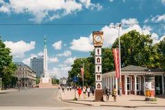 Riga, Lettland Die Leute, die nahe lokalem Markstein gehen, sind Laima-Uhr lizenzfreies stockbild