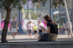 RIGA, LETTLAND - 18. JULI 2018: Eine junge Frau sitzt auf der Bank am Rand der Straße und an den Blicken am Telefon lizenzfreie stockfotos