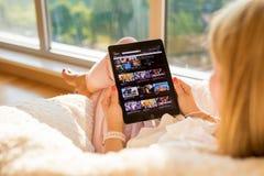 Riga Lettland - Juli 21, 2018: Kvinna som ser den videopd websiten för Amazon Prime på iPad arkivfoton