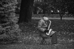 RIGA, LETTLAND - JULI 2017: Schwarzweiss-Bild des plaing Saxophons des alten Mannes in einem Park Lizenzfreies Stockbild