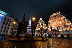 RIGA, LETTLAND - 17. MÄRZ 2019: Professioneller langer Belichtungsschuß nachts regnerisches Haus von Mitessern, Statue von gegenü stockbilder