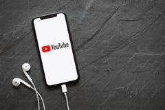 Riga, Lettland - 25. März 2018: Spätestes Generation iPhone X mit YouTube-Logo auf dem Schirm lizenzfreie stockfotografie
