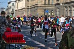 Riga, Lettland - 19. Mai 2019: Auslese-männliche Läufer, die den Erfrischungspunkt erschöpft führen stockfotos
