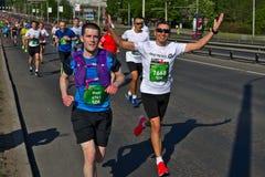 Riga, Lettland - 19. Mai 2019: Glückliche kaukasische Stutenmarathonläuferhände oben mit Sonnenbrille lizenzfreie stockfotografie
