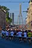 Riga, Lettland - 19. Mai 2019: Marathonläufer, die zu Vansu-Brücke ankommen stockfotos