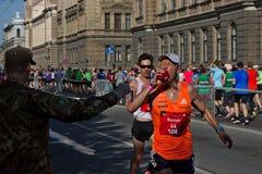 Riga, Lettland - 19. Mai 2019: Römisches darstellendes Wasser des Auslese-männlichen Läufers zu hes Mund stockbilder