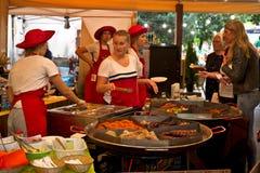 Riga Lettland - Maj 24 2019: Kvinnor som tjänar som mat för besökare av festivalen arkivbilder