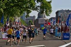 Riga Lettland - Maj 19 2019: Maratonlöpare som når frihetsstatyn med traditionellt beklädde hejaklacksledare, ger höga pickolaflö royaltyfri foto