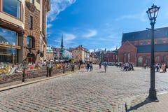 RIGA LETTLAND - MAJ 06, 2017: Sikten på de kulöra hemtrevliga gamla husen, kyrkor och kupolen kvadrerar med gatakaféer som är lok royaltyfria bilder