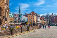 RIGA LETTLAND - MAJ 06, 2017: Sikten på de kulöra hemtrevliga gamla husen, kyrkor och kupolen kvadrerar med gatakaféer som är lok arkivfoto