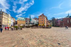RIGA LETTLAND - MAJ 06, 2017: Sikten på de kulöra hemtrevliga gamla husen, kyrkor och kupolen kvadrerar med gatakaféer som är lok fotografering för bildbyråer