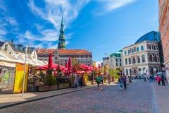 RIGA LETTLAND - MAJ 06, 2017: Sikten på de kulöra hemtrevliga gamla husen, kyrkor och kupolen kvadrerar med gatakaféer som är lok royaltyfria foton