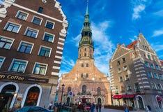 RIGA LETTLAND - MAJ 06, 2017: Sikten på kyrka för ` s för Riga ` s StPeter, restauranger, kafét och mest nearest hus lokaliseras  royaltyfria bilder