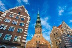 RIGA LETTLAND - MAJ 06, 2017: Sikten på kyrka för ` s för Riga ` s StPeter, restauranger, kafét och mest nearest hus lokaliseras  arkivfoton