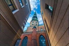 RIGA LETTLAND - MAJ 06, 2017: Sikten på kyrkan för ` s för torn- eller kupolRiga ` s StPeter med klockan och vindflöjeln är locat fotografering för bildbyråer