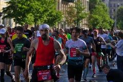 Riga Lettland - Maj 19 2019: Skr?mmande sk?ggig man som k?r i maratonfolkmassa arkivfoto