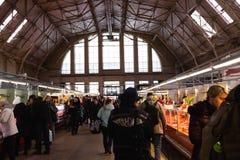 RIGA LETTLAND - MARS 16, 2019: Paviljong för kött Riga för central marknad, folk som köper ny mat - tidigare zeppelinarehangarer  royaltyfri foto