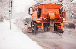 RIGA, LETTLAND - 2016 AM 4. NOVEMBER: Schneereinigerauto säubert schneebedeckten ro Lizenzfreies Stockfoto