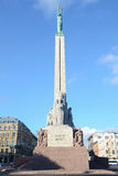 Riga, Lettonia - 10 agosto 2014 - guardia onoraria di Solider fa una pausa il monumento di libertà al di sotto del giorno nuvolos Fotografia Stock Libera da Diritti