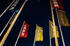 Riga, Lettonia - 3 aprile 2019: Bandiere di IKEA durante la sera scura e vento - cielo blu nei precedenti fotografie stock libere da diritti