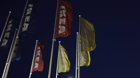 Riga, Lettonia - 3 aprile 2019: Bandiere di IKEA durante la sera scura e vento - cielo blu nei precedenti stock footage