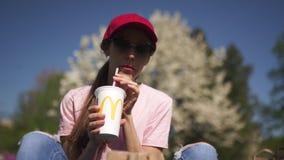 RIGA, LETTONIA - 28 APRILE 2019: Riuscita donna di affari che mangia il cheesburger dell'hamburger del Big Mac di McDonalds e che archivi video