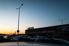 RIGA, LETTONIA - 3 APRILE 2019: Segno di marca di IKEA durante la sera scura e vento - cielo blu nei precedenti fotografie stock libere da diritti