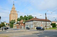 RIGA/LETTONIA - 27 luglio 2013: Via in città di Riga con edificio alto dell'accademia delle scienze lettone nel fondo Fotografie Stock