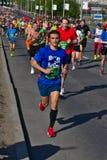 Riga, Lettonia - 19 maggio 2019: Giovane corridore maratona con le cuffie con la grande folla a fondo immagini stock libere da diritti
