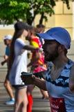 Riga, Lettonia - 19 maggio 2019: Uomo barbuto che corre con la tazza in sua mano fotografie stock