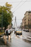 Riga, October 4, 2017: People on the rainy cloudy juni cross the road. Cars are driving along the road stock photos