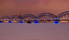 Riga railway bridge at night time. In winter Stock Photos