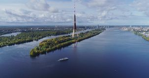 TV tower Riga city Drone flight, Zakusala island, Dugava river clouds. Riga TV tower, Daugava river Drone flight, passenger ship voyage, clouds in Latvia nature stock video footage