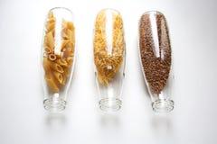 Rigate de Penne, pastas del huevo y alforfón almacenados en las botellas de cristal Foto de archivo libre de regalías