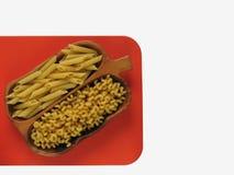 Rigate e cavatappi del penne della pasta in ciotola di legno sul bordo arancio immagini stock libere da diritti