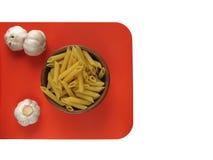 Rigate penne макаронных изделий в деревянных шаре и чесноке на оранжевой доске Стоковые Фото