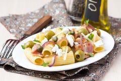 Ζυμαρικά Rigatoni με το μπέϊκον, πράσινες ελιές, τυρί φέτας, κόκκινο κρεμμύδι Στοκ εικόνες με δικαίωμα ελεύθερης χρήσης