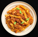 Rigatoni Pasta with Bolognese Sauce. Rigatoni pasta with a rich beef and tomato ragu. Garnished with basil leaves and freshly ground pepper Stock Photo