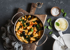 Rigatoni pasta with chickpeas, spinach and olives in a tomato sauce on a dark background, top view. Royalty Free Stock Image