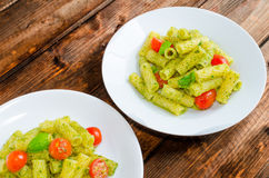 Rigatoni pasta with genoese pesto and sherry tomato. On wood royalty free stock photography