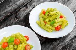 Rigatoni pasta with genoese pesto and sherry tomato. On wood royalty free stock image