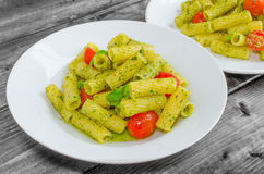Rigatoni pasta with genoese pesto and sherry tomato. On wood royalty free stock images