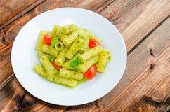 Rigatoni pasta with genoese pesto and sherry tomato. On wood royalty free stock photos