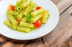 Rigatoni pasta with genoese pesto and sherry tomato. On wood stock photography
