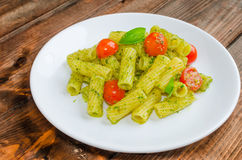 Rigatoni pasta with genoese pesto and sherry tomato. On wood royalty free stock photo