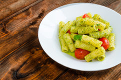 Rigatoni pasta with genoese pesto and sherry tomato. On wood stock images