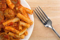 Rigatoni pasta with meatballs and sausage on plate with fork Stock Photo