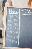 Rigged coin toss. A blackboard counting the number of heads or tails with heads leading over tails Stock Photo